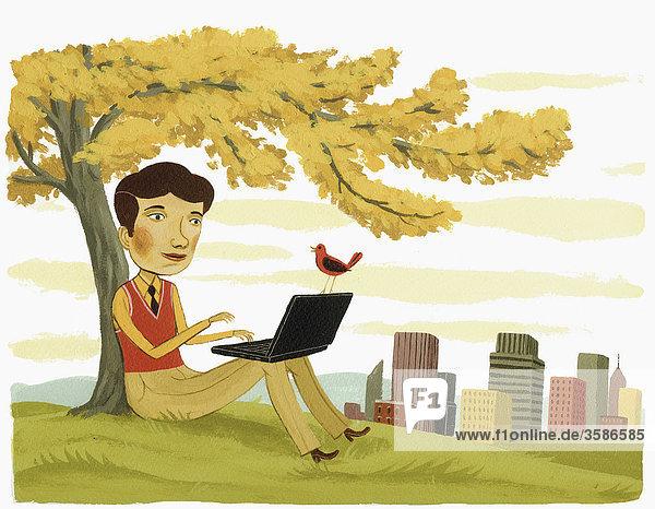 Geschäftsmann benutzt Laptop unter einem Baum
