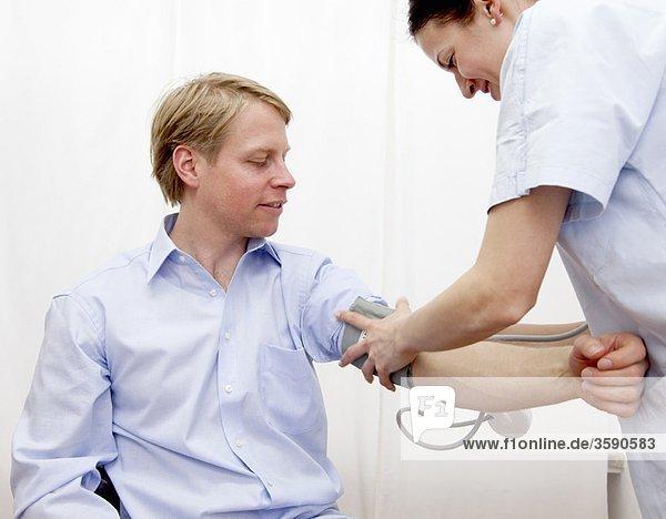 Ärztin  die den Blutdruck nimmt