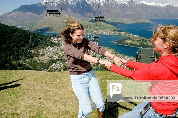 Backpacker portraits of excitement overlooking Lake Wakatipu and the city  South Island  New Zealand