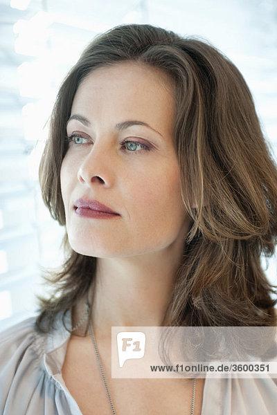 Nahaufnahme einer Frau mit Blick aus dem Fenster