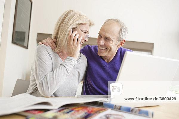 Frau  die mit ihrem Mann auf einem Handy vor einem Laptop sitzt.