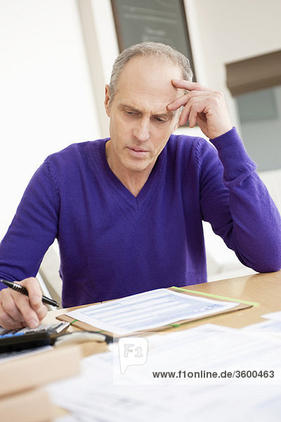 Man using calculator and filling his tax form