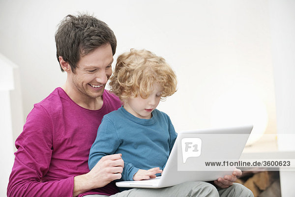 Close-up of a man assisting his son in using a laptop