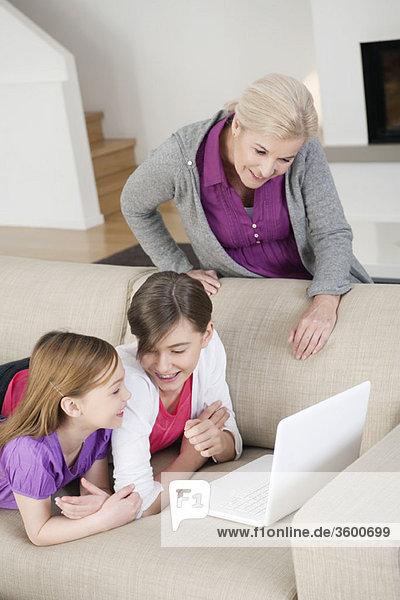 Zwei Mädchen  die mit ihrer Großmutter einen Laptop auf einer Couch benutzen.