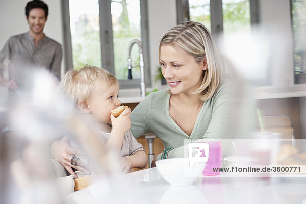 Woman eating breakfast with her son