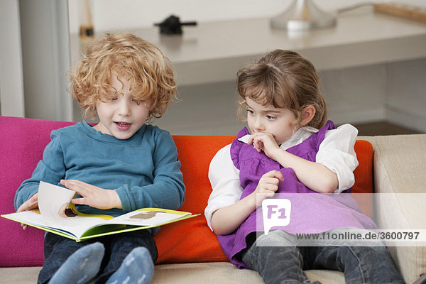 Boy sitting with his sister and reading a book