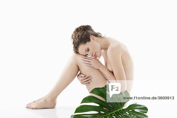 Nackte Frau sitzend mit einem Philodendronblatt neben ihr