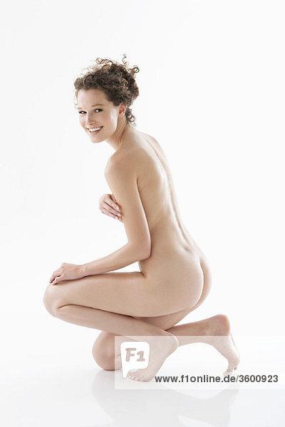 Nackte Frau  die ihre Brüste bedeckt und lächelt.