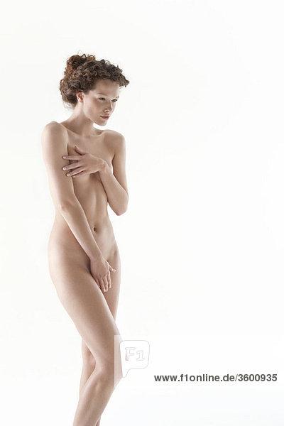 Nackte Frau  die die Leiste mit der Hand bedeckt.