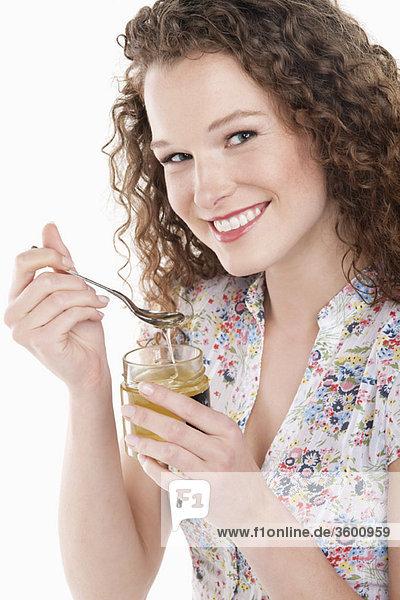 Porträt einer Frau beim Honigessen