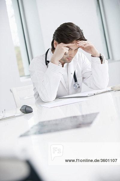 Ein männlicher Arzt sitzt in seinem Büro und sieht verärgert aus.
