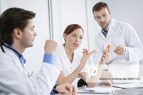 Drei Ärzte untersuchen die Medizin