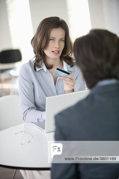 Geschäftsfrau  die einem Geschäftsmann eine Kreditkarte zeigt