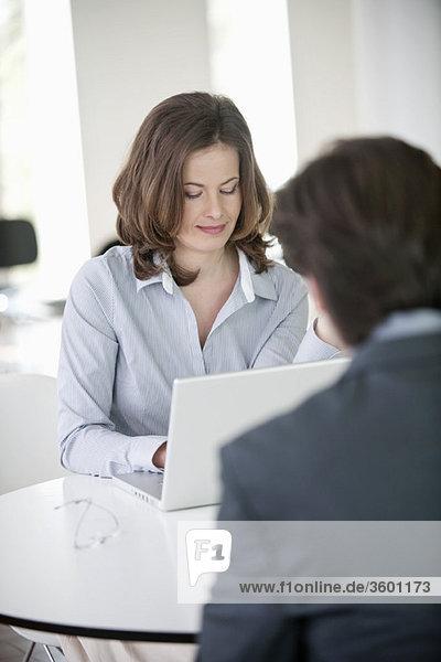 Geschäftsfrau sitzt vor einem und Geschäftsmann arbeitet am Laptop