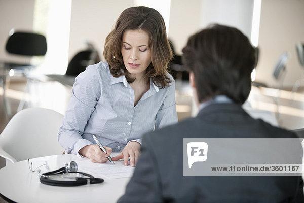 Frau schreibt ein Dokument mit einem Mann  der vor ihr sitzt.