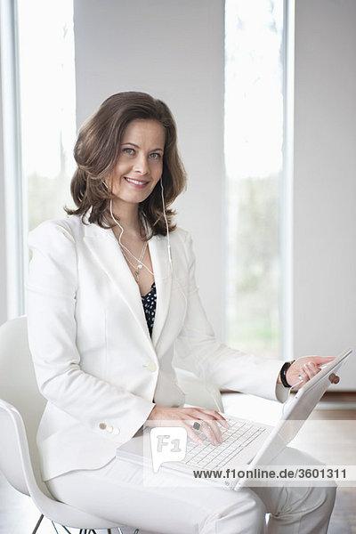 Geschäftsfrau  die einen MP3-Player hört und einen Laptop benutzt