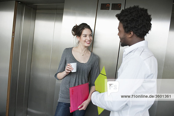 Businesswoman holding a disposable cup and talking to her colleague