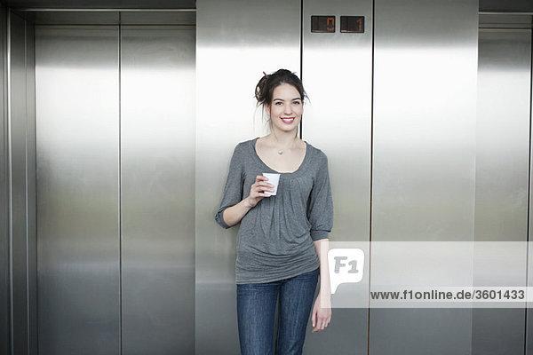 Geschäftsfrau hält einen Einwegbecher und lächelt