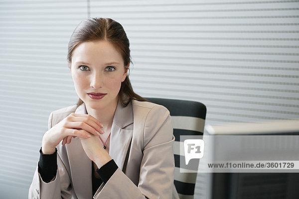 Geschäftsfrau im Büro sitzend