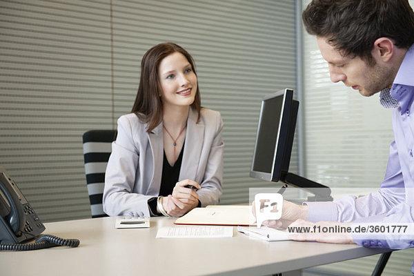 Mann beim Unterschreiben von Dokumenten mit einer Immobilienmaklerin  die vor ihm sitzt