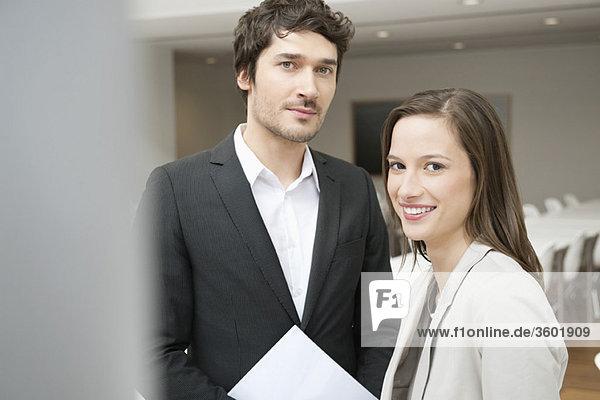 Porträt einer Geschäftsfrau  die mit ihrem Kollegen neben ihr lächelt.