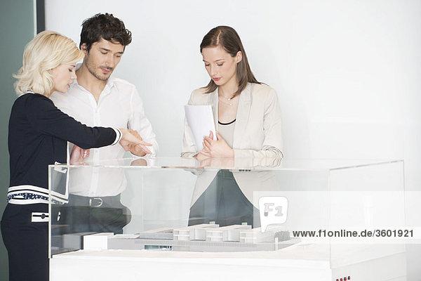 Mann mit zwei Frauen beim Betrachten eines Architekturmodells