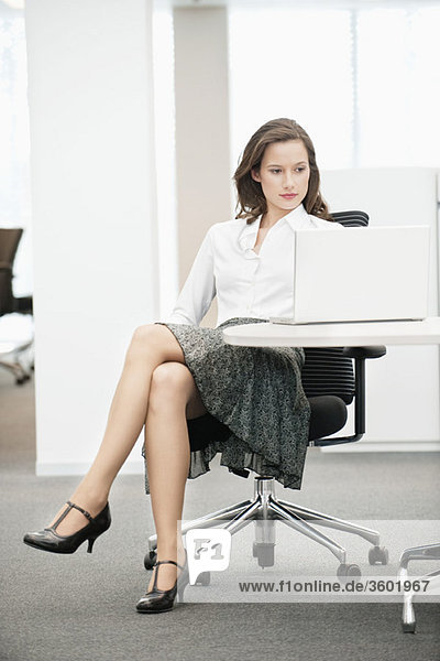 Businesswoman sitting in an office and using a laptop