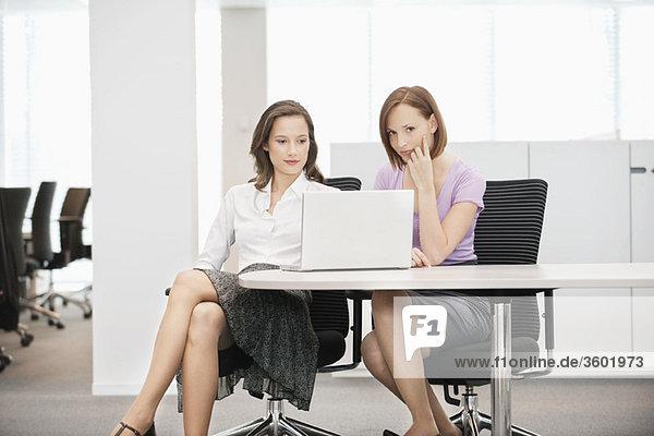 Zwei Geschäftsfrauen  die in einem Büro arbeiten.