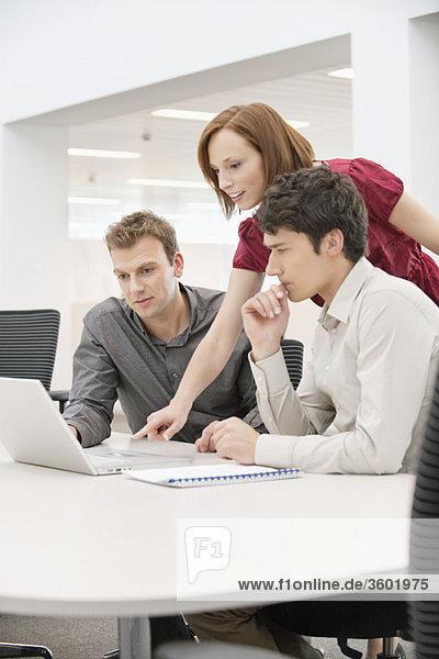 Geschäftsfrau mit zwei Geschäftsleuten im Büro