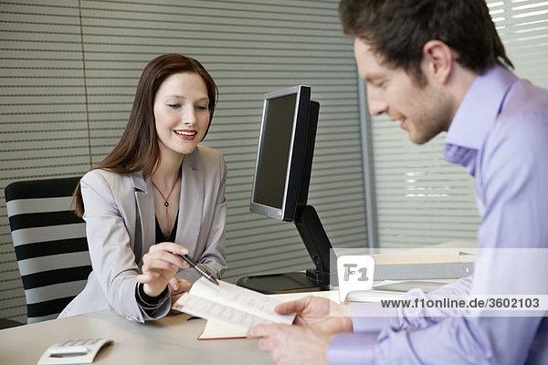 Immobilienmaklerin zeigt einem Mann eine Broschüre