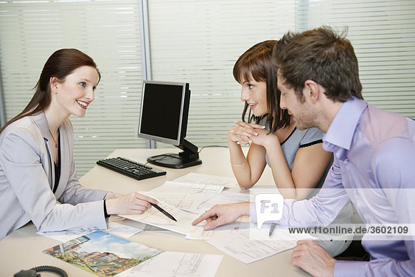 Immobilienmaklerin zeigt einem Paar eine Broschüre