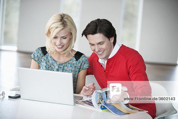 Paar mit einem Laptop und Lächeln