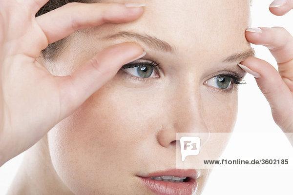 Nahaufnahme einer Frau mit massierenden Augenbrauen