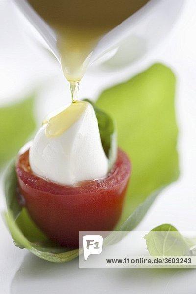 Olivenöl auf Tomate mit Mozzarella und Basilikum giessen