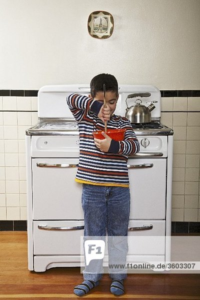 Six Year Old Boy Stirring Bowl In Front of a Stove in the Kitchen