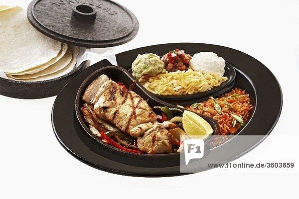 Hähnchen-Fajita mit Beilagen und Tortillas