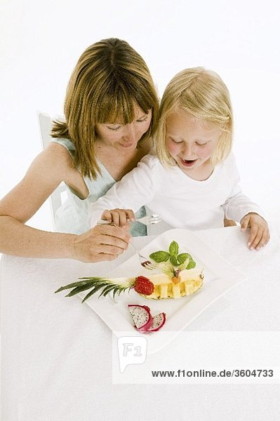 Mutter und Tochter essen Obst vom Obstteller