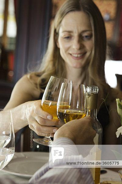 Frau klirrt mit Begleiterin im Restaurant