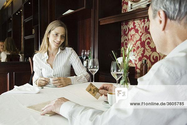 Reife Paare beim Kaffee im Restaurant  Mann  der sich auf die Bezahlung mit Kreditkarte vorbereitet.