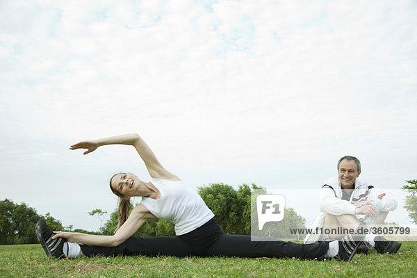 Reife Paare beim Stretching im Park
