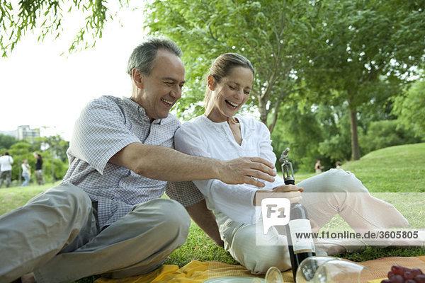 Erwachsenes Paar beim Picknick im Freien,  Flasche Wein öffnen