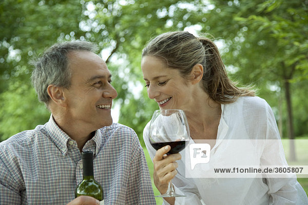 Reife Paare genießen Rotwein im Freien