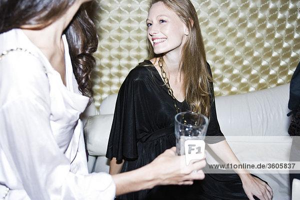 Junge Frau im Nachtclub im Gespräch mit Freunden