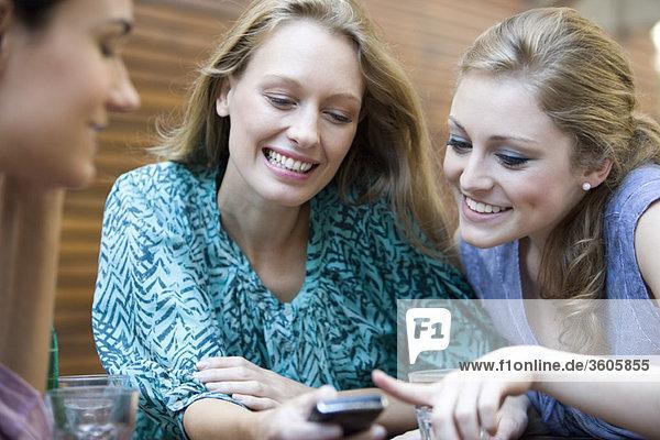 Junge Frau zeigt Freunden ihr Handy