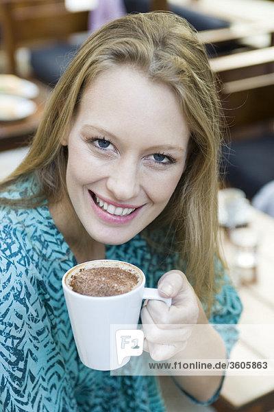 Junge Frau genießt Tasse Cappuccino  Portrait