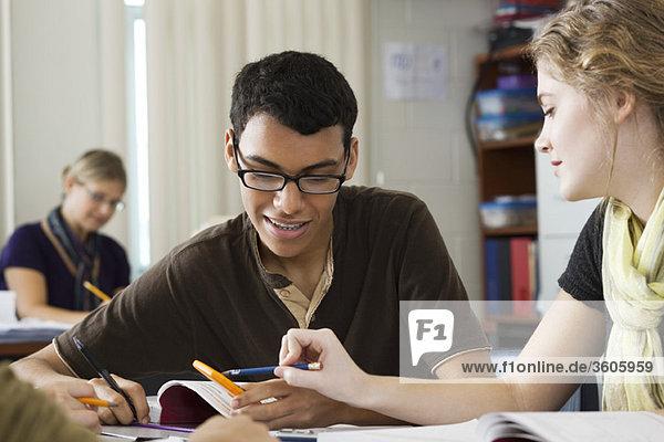 Mitschülerinnen und Mitschüler  die gemeinsam an einer Mathematikaufgabe arbeiten