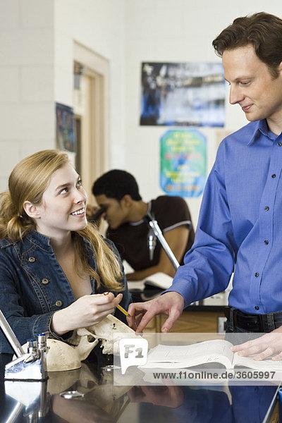 Lehrer hilft Schüler im naturwissenschaftlichen Unterricht