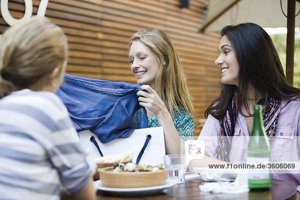 Freunde beim gemeinsamen Mittagessen im Outdoor-Café  eine Frau zeigt neue Kleidung in der Einkaufstasche