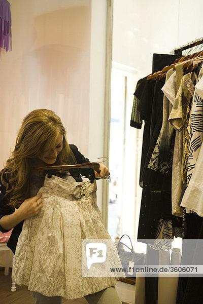 Frau schaut sich den Rock im Bekleidungsgeschäft an