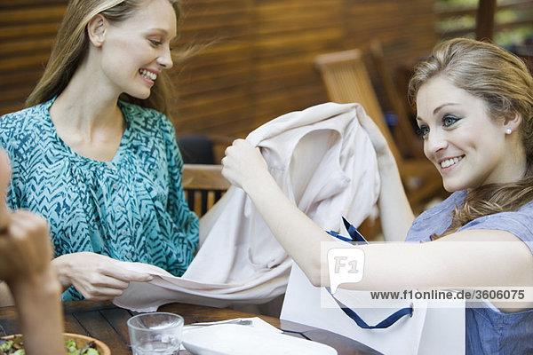 Freunde zusammen im Outdoor-Café  eine Frau zeigt neue Kleidung in der Einkaufstasche